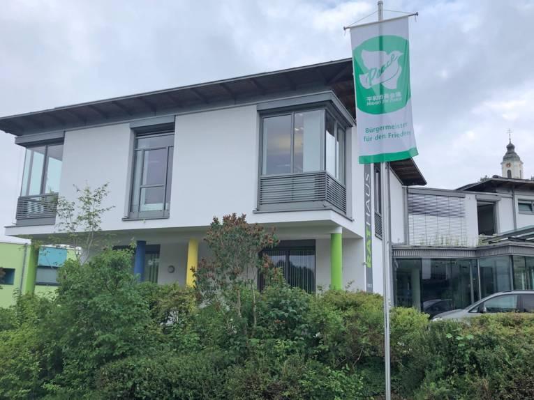 Die grün-weiße Mayors for Peace-Flagge weht am Flaggenmast vor dem Rathaus der Gemeinde Bodnegg.