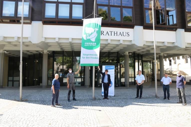 Eine Gruppe von Menschen steht vor dem Rathaus von Bretten um die gehisste Flagge der Bürgermeister für den Frieden.
