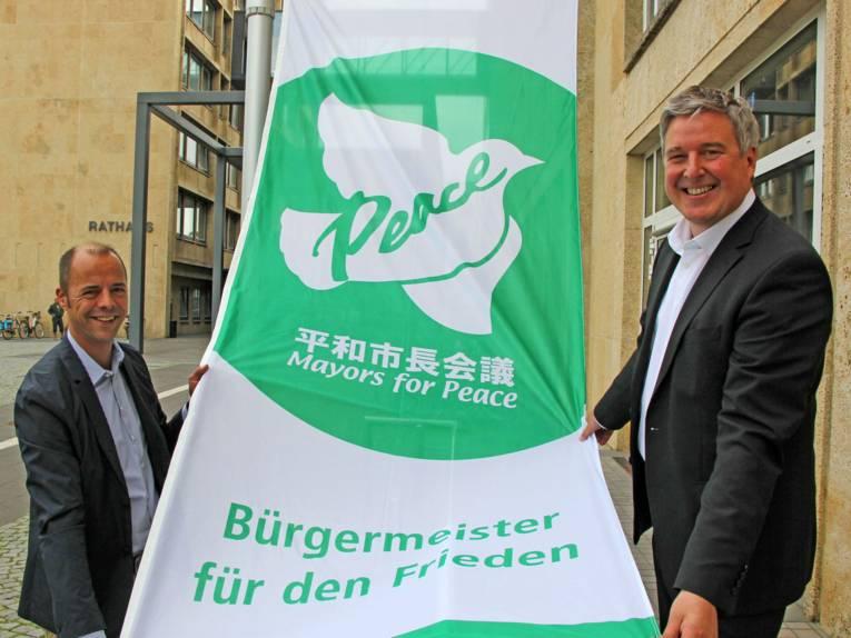 """Bürgermeister und Integrationsbeauftragter der Stadt Gütersloh zeigen die Flagge der """"Bürgermeister für den Frieden"""""""