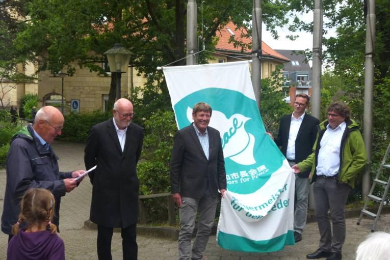 Mayors-for-Peace-Flagge und eine Gruppe Menschen