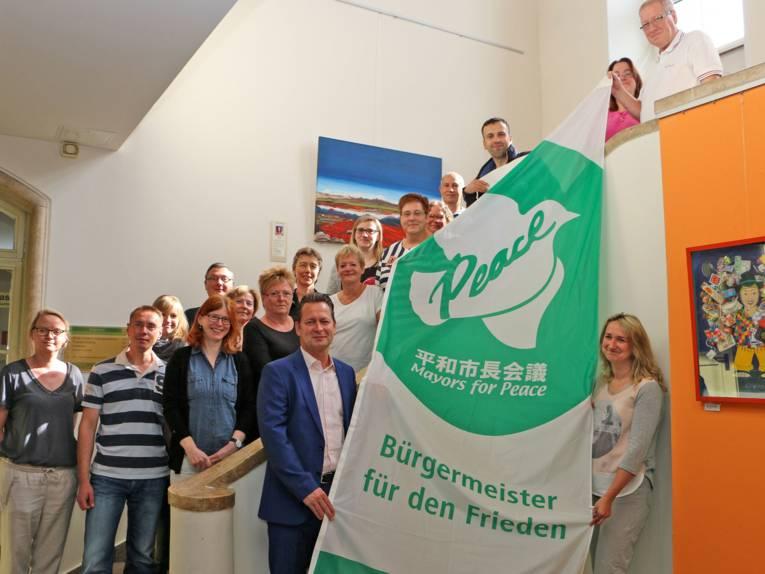 """Auf einer Treppe stehen zahlreiche Beschäftigte der Stadt Hohen Neuendorf und präsentieren gemeinsam mit dem Bürgermeister Steffen Apelt die """"Mayors for Peace"""" Flagge"""