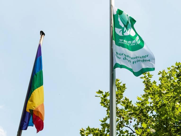 Die Bürgermeister-für-den-Frieden-Flagge neben der Regenbogen-Fahne.