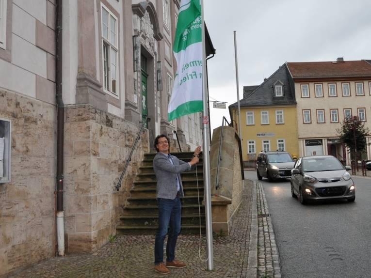 """Vor dem Rathaus in Königsee wird die """"Bürgermeister für den Frieden""""-Flagge gehisst."""