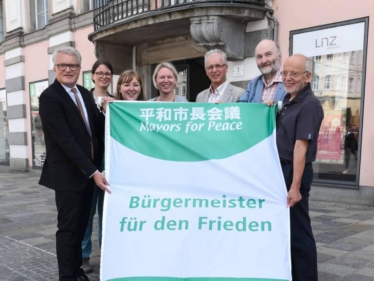"""Bürgermeister Klaus Luger und sechs weitere Personen stehen vor dem Linzer Rathaus und zeigen die Flagge """"Bürgermeister für den Frieden"""", bevor sie gehisst wird."""