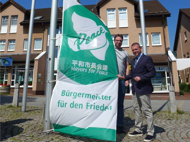 Vor strahlend blauem Himmel wird in Lohfelden die Bürgermeister- für-den-Frieden-Flagge gehisst.