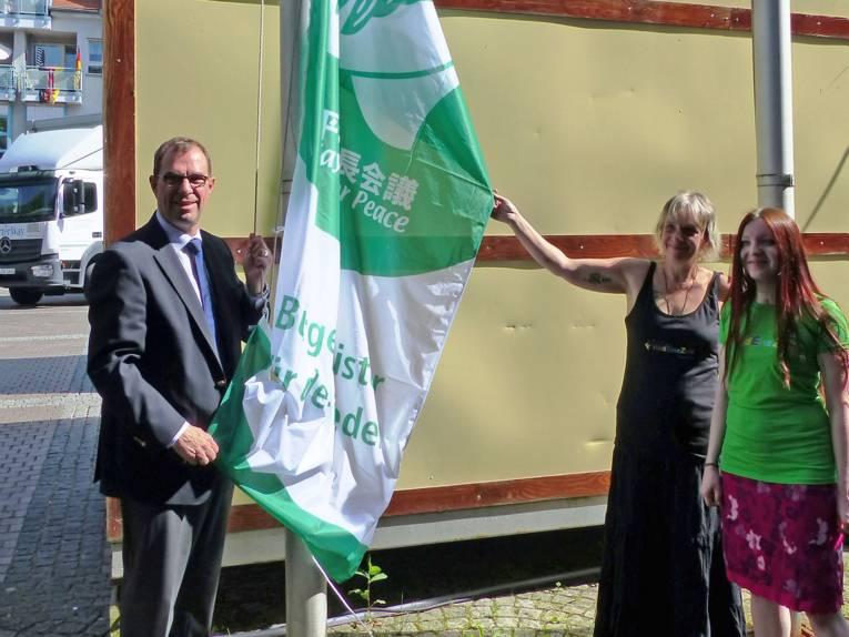 """Mühlackers Oberbürgermeister Frank Schneider mit zwei weiblichen Mitgliedern der Friedensgruppe """"Friedenszeit"""" beim Hissen der """"Mayors for Peace""""-Flagge"""
