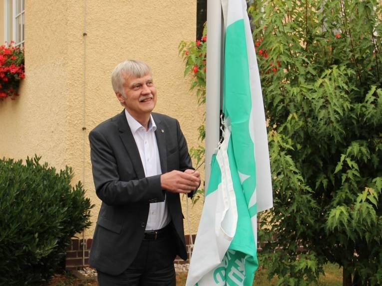 Ein Mann hisst eine Mayors-for-Peace-Flagge