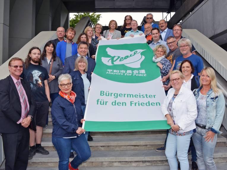 """Auf einer Treppe stehen viele Personen und halten gemeinsam die """"Bürgermeister für den Frieden""""-Flagge"""