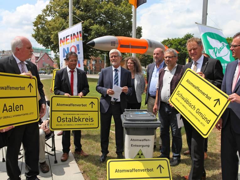 """Mehrere Personen zeigen gelbe Ortsschilder des Ostalbkreises verbunden mit der Forderung nach einem Atomwaffenverbot. Im Hintergrund die """"Nein""""-Flagge und die """"Mayors-for-Peace""""-Flagge."""