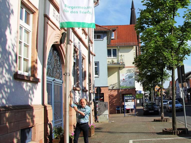 """Bürgermeister Roland Kern beim Hissen der """"Bürgermeister für den Frieden""""-Flagge vor dem Rathaus Ober-Roden"""