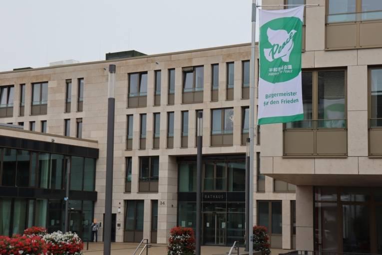 Die Bürgermeister-für-den-Frieden-Flagge vor einem Gebäude.