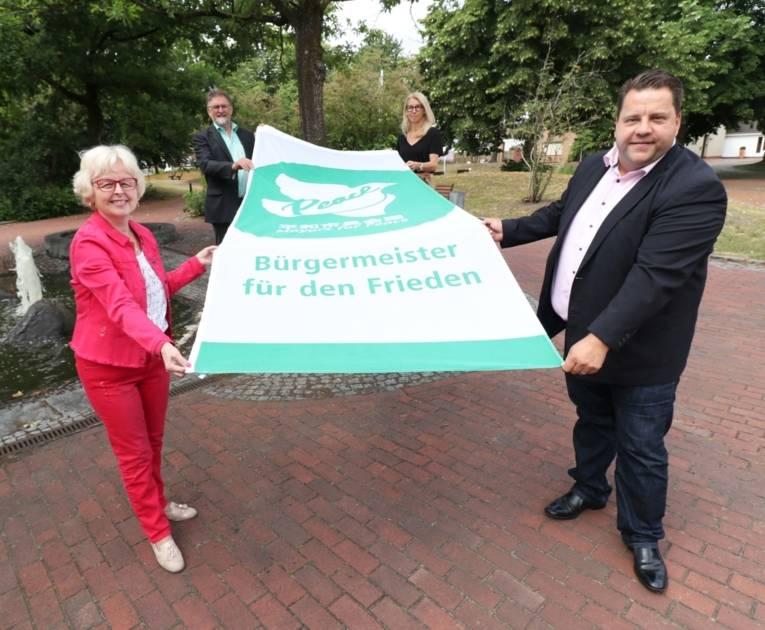 Eine Gruppe von Personen mit der Mayors-for-Peace-Flagge