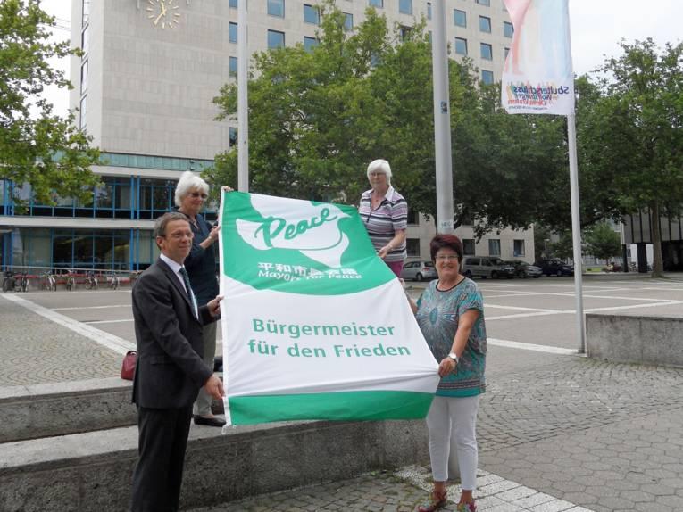 """Oberbürgermeister Klaus Mohrs präsentiert mit den Bürgermeisterinnen Hiltrud Jeworrek und Elke Braun sowie einer vierten Person die Flagge des internationalen Städtenetzwerkes """"Bürgermeister für den Frieden"""" auf dem Wolfsburger Rathausplatz."""
