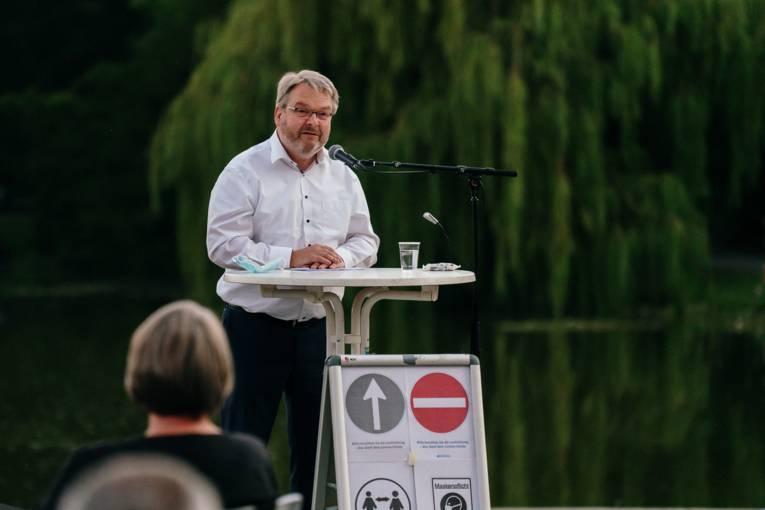 Bürgermeister Thomas Herrmann bei einer Rede, im Hintergrund der Maschpark.