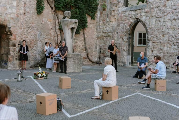 Mehrere Menschen sitzen auf Pappkartons verteilt in der Aegidienkirche, im Hintergrund ein Saxophonspieler.