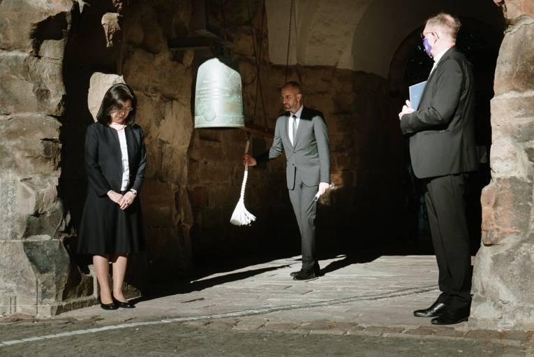 Oberbürgermeister Onay schlägt die Friedensglocke an.