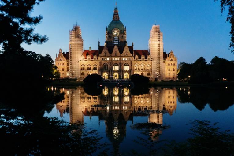 Das Neue Rathaus in der Dunkelheit, auf dem Maschteich bunte Lampions.
