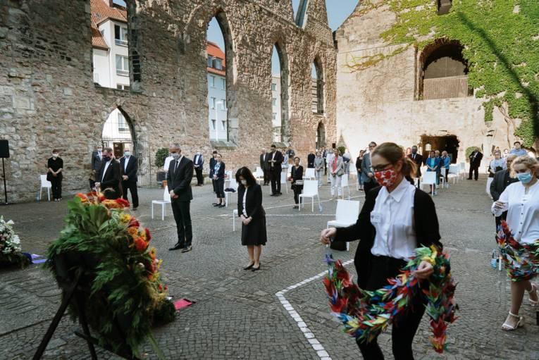 Junge Menschen legen Papierkraniche am Altar der Aegidienkirche ab.