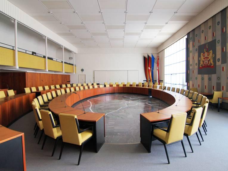 Ein großer Raum, um dessen Mitte Tische gruppiert sind, an denen Stühle stehen