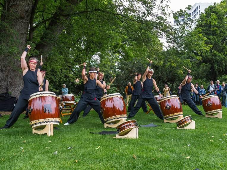Frauen in einem Park, die Trommeln schlagen.