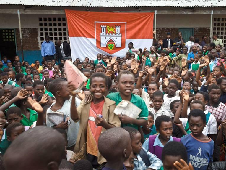 Kinder und Jugendliche in Blantyre haben sich in einem Hof versammelt; im  Hintergrund die Fahne mit dem Wappen Hannovers