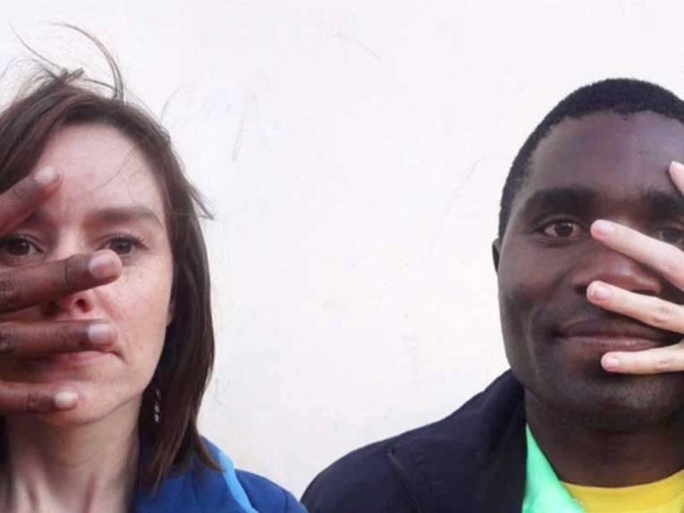 Links wird das Gesicht einer Frau mit weißer Hautfarbe zum Teil von einer schwarzen Hand überdeckt und rechts das Gesicht eines Mannes mit dunkler Hautfarbe zum Teil von einer weißen Hand.