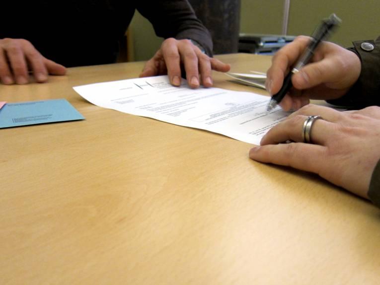 Nachgestellte Szene: Ein Wahlhelfer übergibt die Briefwahlunterlagen