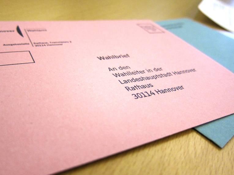 Der lachsfarbene Umschlag, der in die Wahlurne geworfen wird