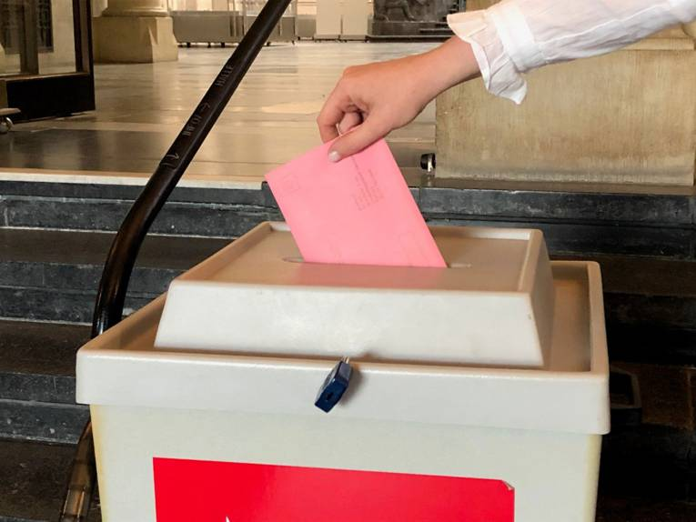 Ein Briefumschlag wird in eine Wahlurne gesteckt (nachgestellte Szene).