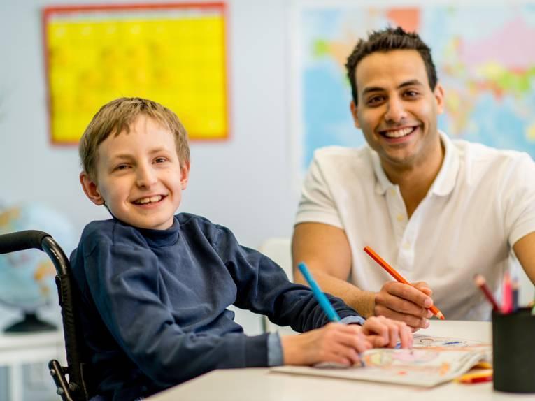 Ein Junge im Rollstuhl sitzt an einem Tisch und malt in einem Heft, daneben sitzt ein junger Mann und unterstützt ihn dabei.