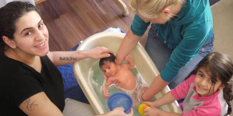 Ein neugeborenes Baby wird liebevoll in einer Babywanne gebadet