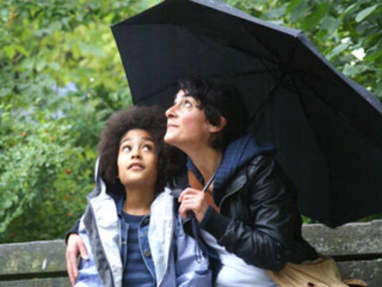 Ein großer Schirm schützt Mutter und Kind