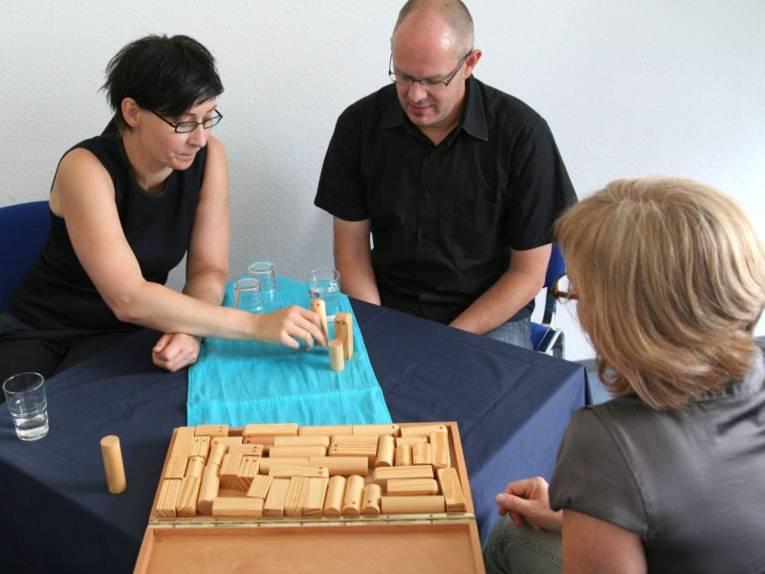 Drei Personen an einem Tisch erarbeiten eine Lösung