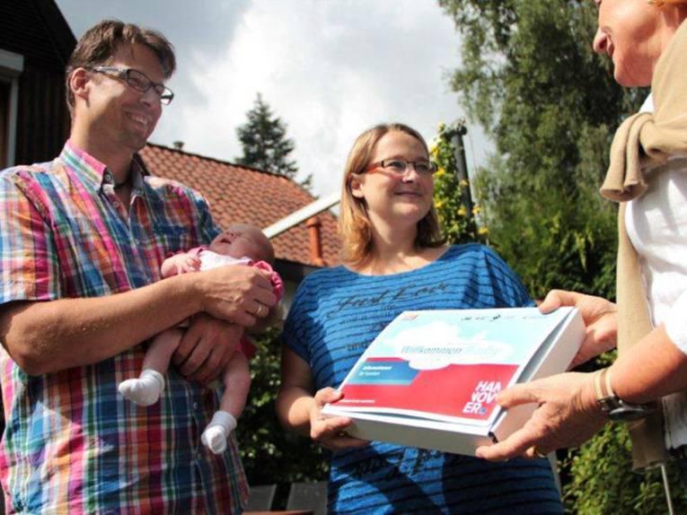 Eltern mit einem Baby auf dem Arm erhalten das Willkommenspaket der Stadt