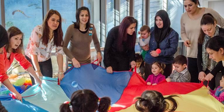 Junge Mütter und ihre Kinder spielen gemeinsam