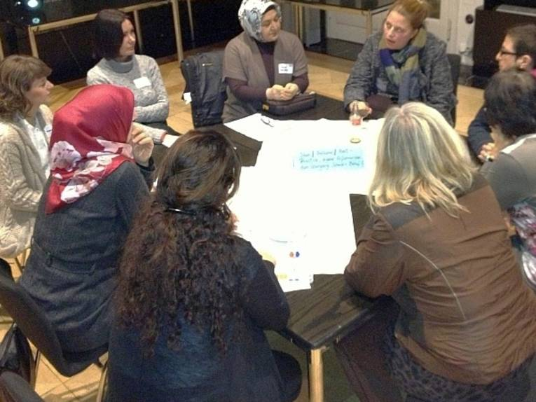Interessierte sitzen an einem Tisch und diskutieren