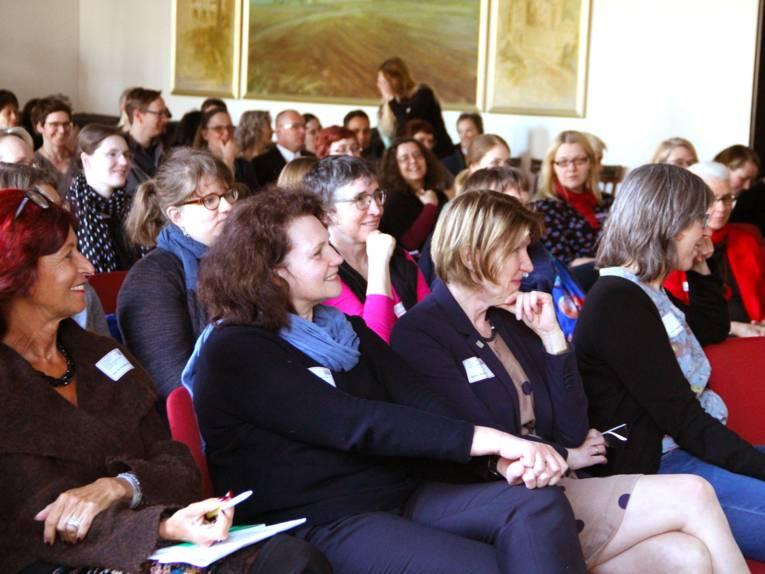 In einem Vortragsraum sitzen viele Personen.