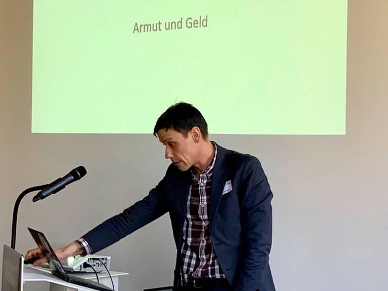 Professor Dr. Holger Ziegler steht am Redepult und schaut auf das Display.