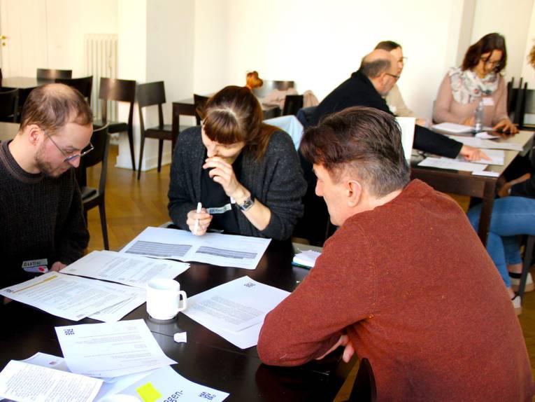 Mehrere Personen sitzen mit Unterlagen an Tischen und diskutieren miteinander.