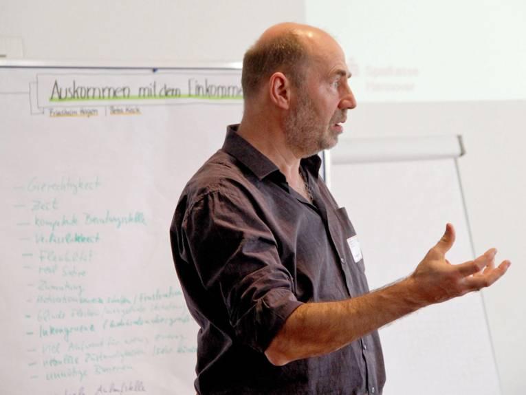 """Herr Hagen steht vor einer Stellwand, auf der Punkte zum Thema """"Auskommen mit dem Einkommen"""" notiert sind."""