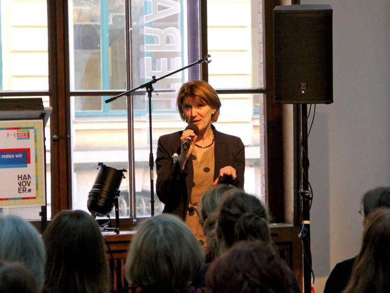 Frau Kuhlmey hält ein Mikrophon in der Hand und spricht in einem Saal vor vielen Zuhörerinnen und Zuhörern.