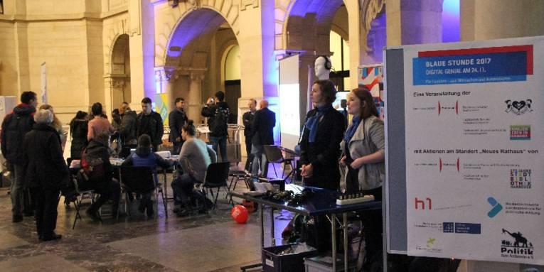In der blau ausgeleuchteten Rathaushalle sind neben den Stadtmodellen Tische mit Monitoren aufgebaut, an denen verschiedene Personen sitzen und sich informieren. Im Vordergrund stehen neben einer Stellwand mit dem Veranstaltungsplakat zwei Frauen hinter einem Tisch, die man bei Fragen ansprechen kann.