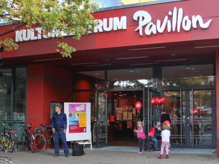 Der Eingang zum Kulturzentrum Pavillon an der Lister Meile: eine Frau verteilt gasgefüllte rote Luftballons an Kinder, ein Mann steht wartend neben dem Veranstaltungsplakat.