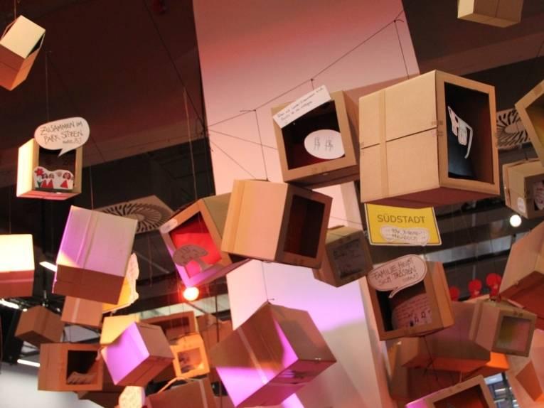 Eine Installation aus Kartons hängt unter der Decke im Foyer des Pavillons am Raschplatz. Die Kartons enthalten unter anderem Kinderzeichnungen und Sprechblasen. Zwischen den Kartons hängen Ortsschilder mit den Namen hannoverscher Stadtteile.