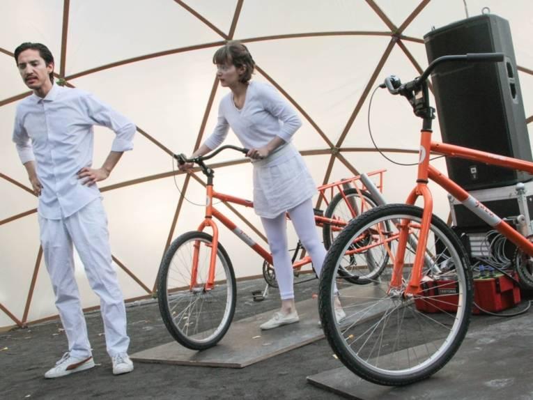 Ein Mann und eine Frau, ganz in weiß gekleidet, stehen unter einer zeltartigen Kuppel aus Holz und Folie bei zwei Fahrrädern, die an ein Gerät mit vielen Kabeln angeschlossen sind.