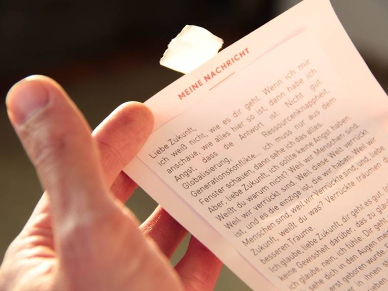 """Eine Hand hält ein Blatt, auf dem unter der Überschrift """"Meine Nachricht"""" ein längerer Text mit den Worten """"Liebe Zukunft..."""" beginnt."""