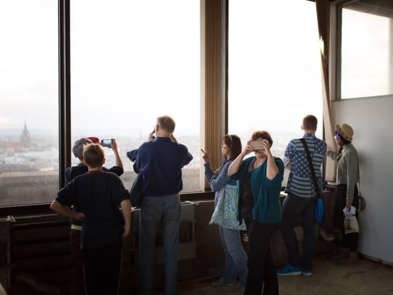Kinder und Erwachsene stehen an einer Fensterfront, durch die man unter anderem die Marktkirche erkennen kann. Im Vordergrund schaut eine Frau durch eine Konstruktion aus Pappe mit optischen Linsen.