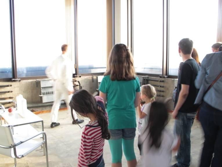 Ein Mann, ganz in weiß gekleidet, geht an einer Fensterfront entlang. Im Bildvordergrund stehen Kinder und Erwachsene, die ihn beobachten oder an ihm vorbei aus den Fenstern schauen.