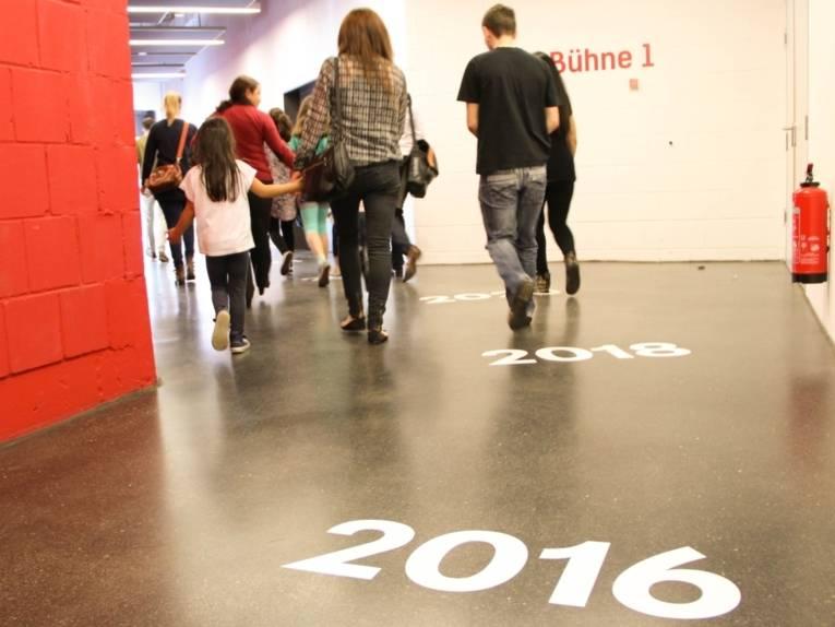 Ein Flur mit einer roten Wand links und einer weißen Wand rechts, auf dem Boden die Abfolge der Zahlen 2016, 2018, 2020... Kinder und Erwachsene folgen dem Flur in aufsteigender Folge der Zahlen.