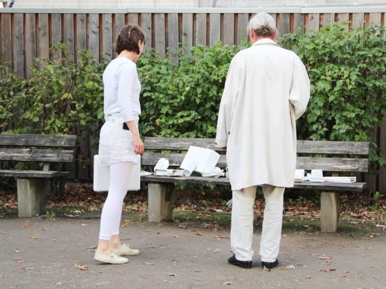 Eine junge Frau und ein älterer Herr, beide ganz in weiß gekleidet, stehen vor einer Parkbank, auf der weiße Objekte liegen, die sich als Abfälle identifizieren lassen.
